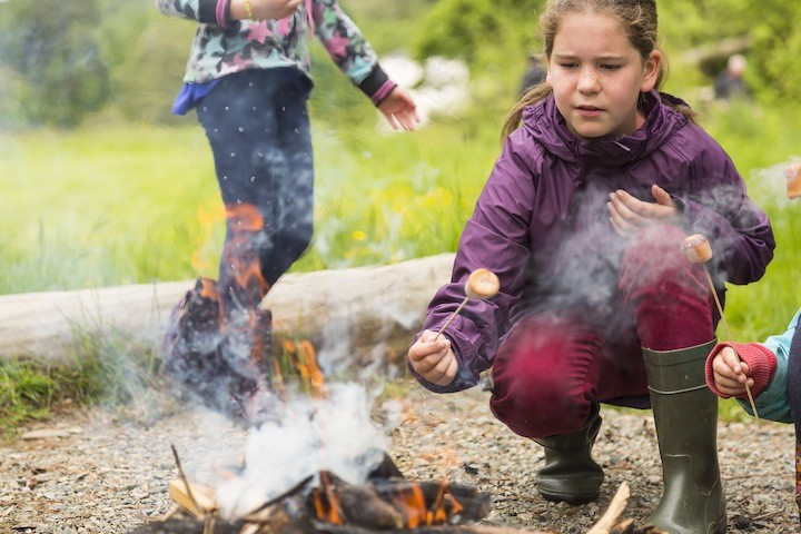 A child toasting marshmallows over an open camp fire at Colby Woodland Garden, Pembrokeshire. The garden is named after Welsh landowner John Colby (1751-1823), who originally came to the area in the 1790s to mine coal. Today, the woodland garden features a wild flower meadow, stream, and colourful walled garden.