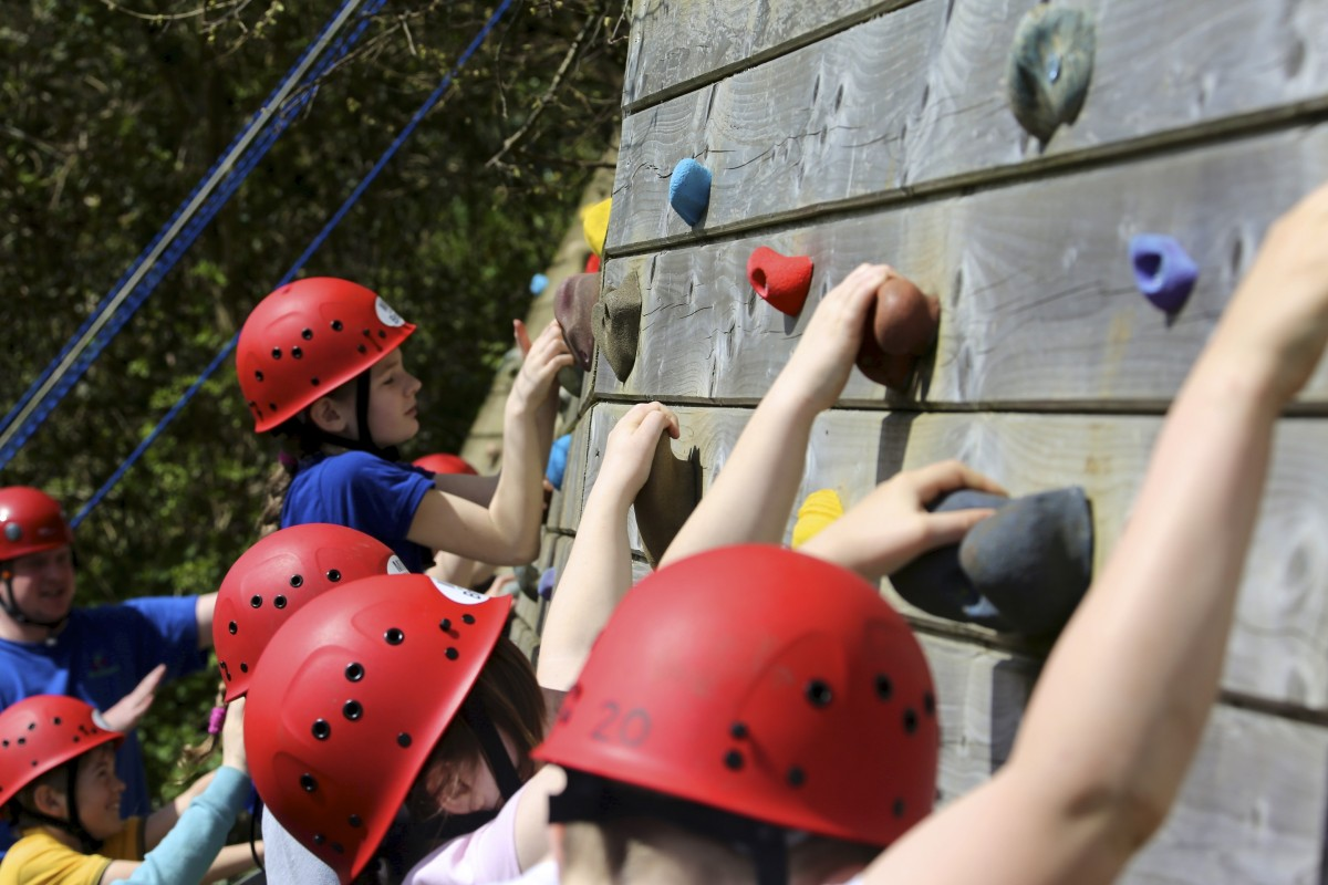 Kids the red safety helmets on climbing wall