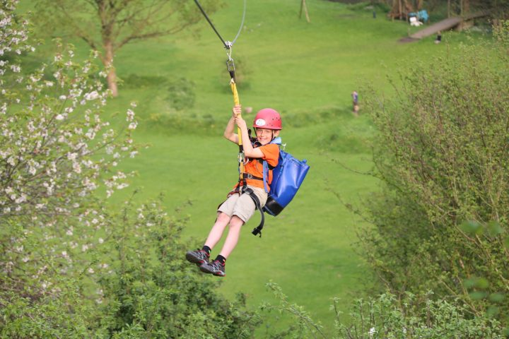 boy with red safety helmet on zip wire over green fields