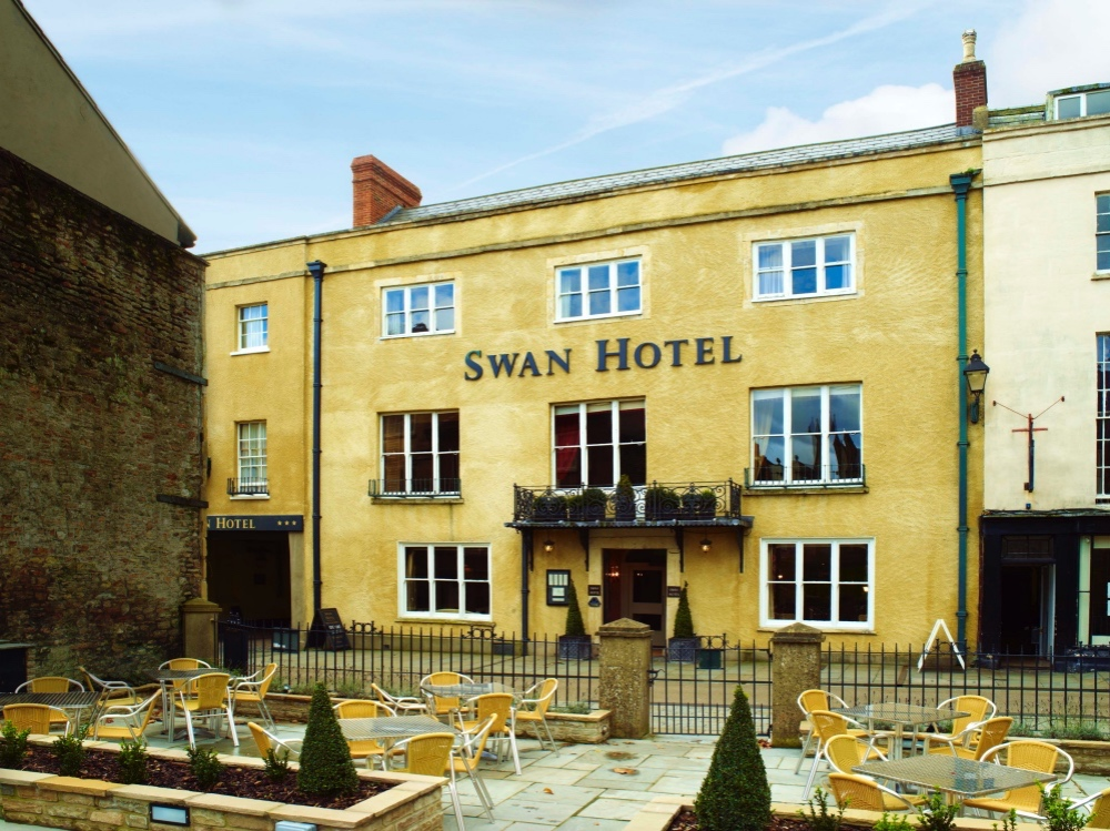 Old golden stone frontage coaching inn with large windows and tables and chairs outside