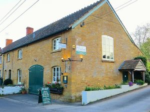 Converted old hamstone farm building with signs, a wooden porch in somerset village