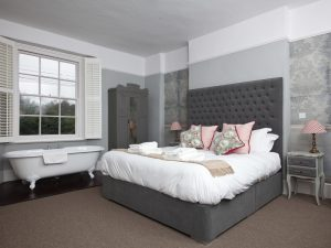 Bedroom with double bed, grey padded headboard pink cushions and claw foot bath