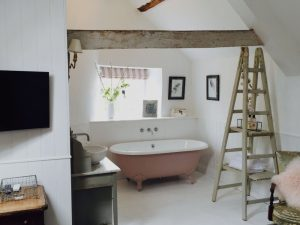 Pink claw foot bath with ladder shelves in white bathroom with wooden beam