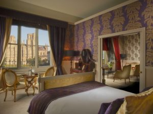 Grand bedroom with ornate furniture with Wells Cathedral through the large window