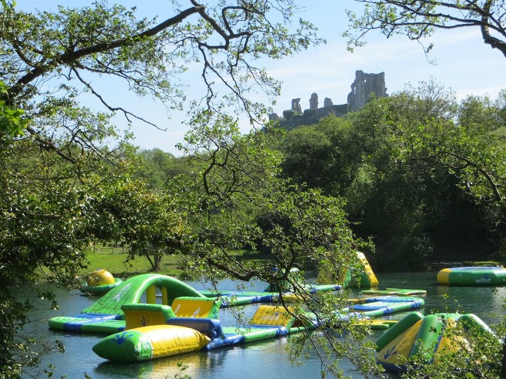 giant floating obstacle course on a lake with corfe castle ruins in the background