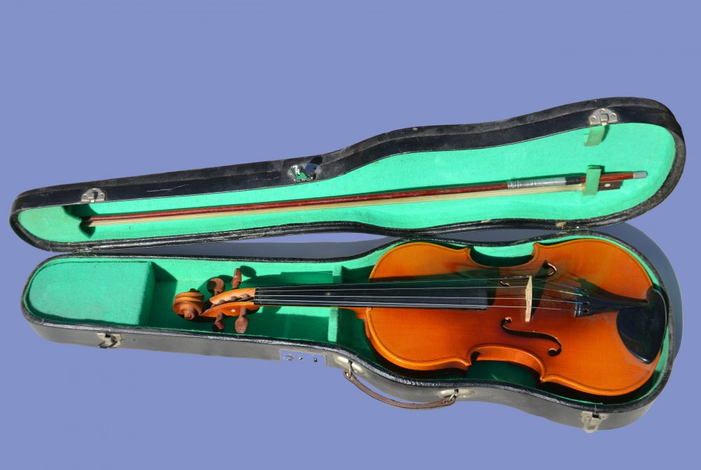 Cut out open violin case wth green lining, brown violin purple background