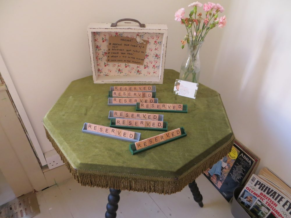 Scrabble letters on green baize card tablewith words reserved vase of flowers