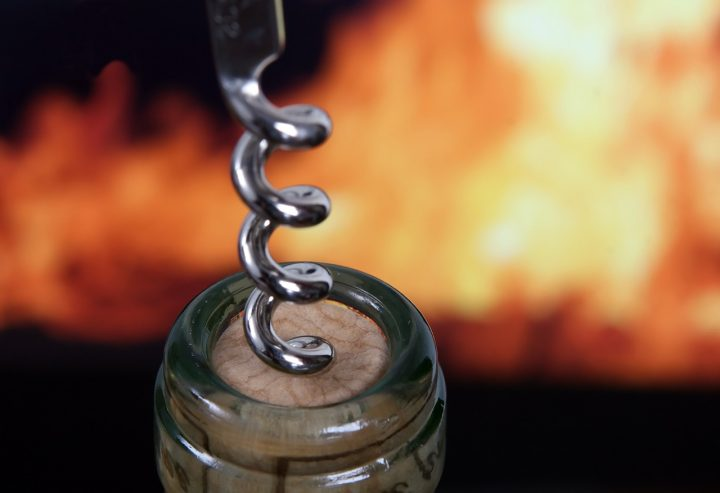 corkscrew coming out of a bottle of wine, bbg fire in the background