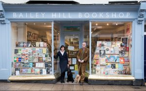 man and woman with dog in doorway of book shop