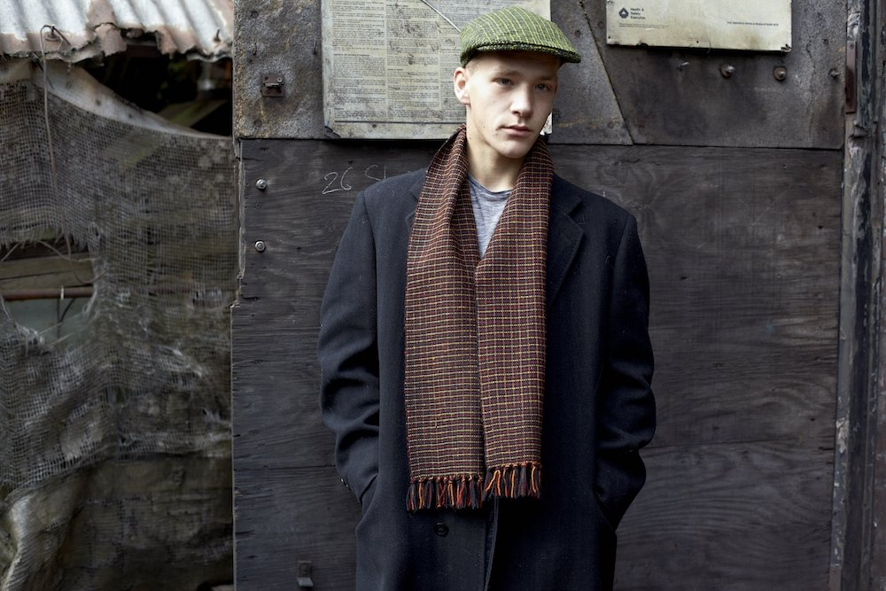 young man with flat cap and scarf