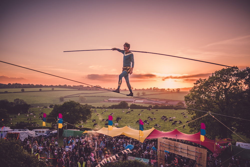 man on high wire tightrope at festival