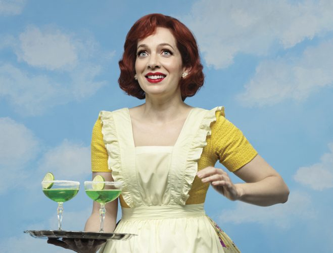 1950s woman with yellow pinafore dress holding two green cocktails