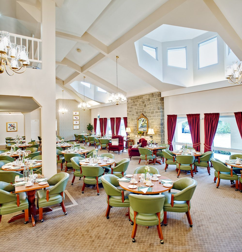 Dining room with tables and chairs and mezzanine in Hawthorns retirement village in Clevedon Somerset in