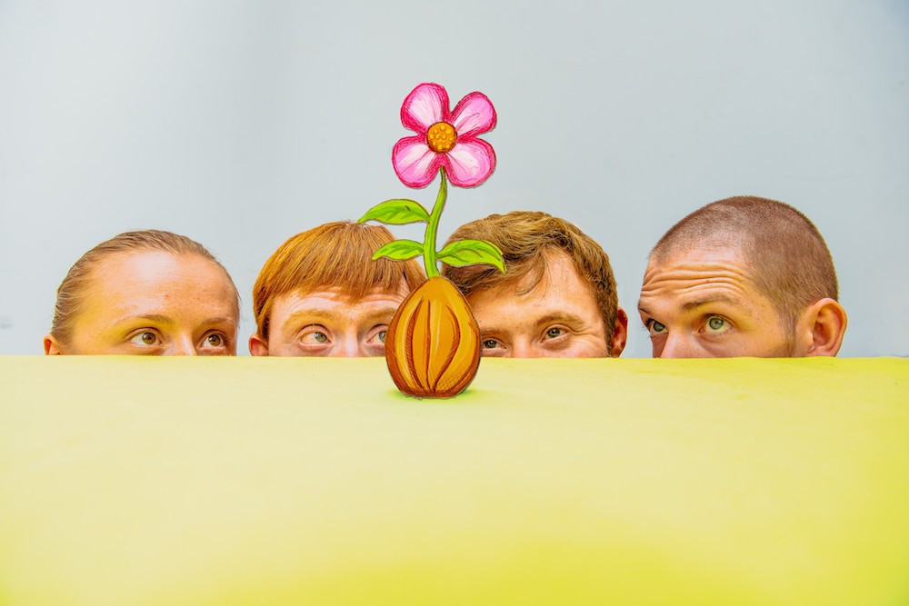 men looking at flower growing out of seed