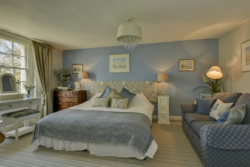 luxury bedroom with double bed blue walls and throw