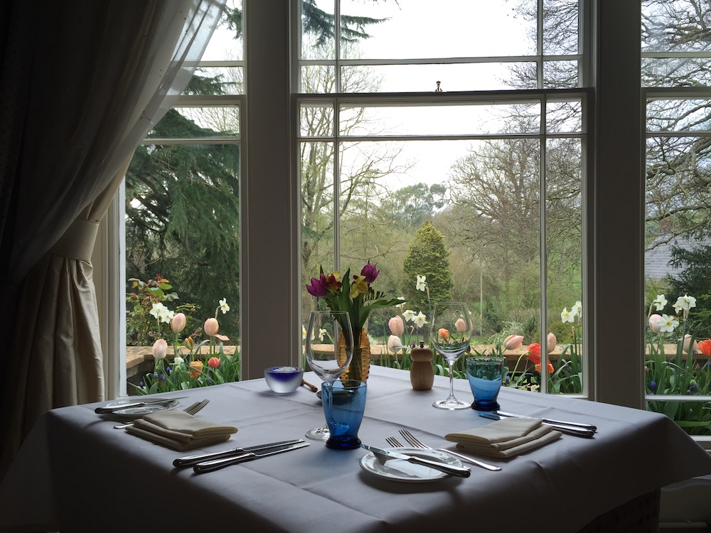 table set for lunch overlooking tulips and gardens beyond