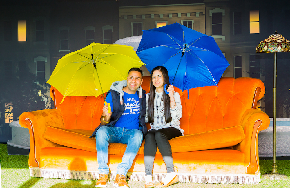 couple with umbrellas sitting on sofa Friends TV show