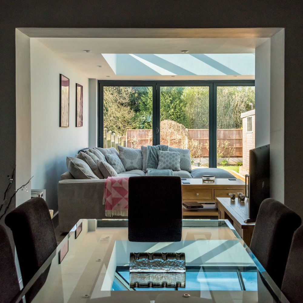 contemporary conservatory with dining table, chairs and sofa looking into garden