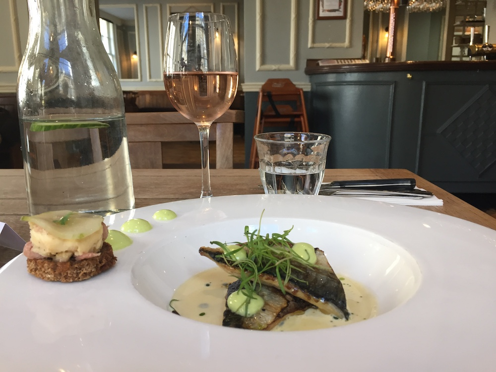 white plate with fillets of mackeral and mussel sauce