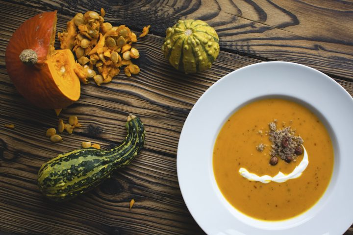 bowl of pumpkin soup with pumpkins