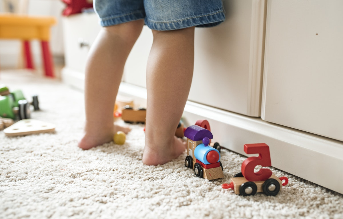 toddlers legs with toys